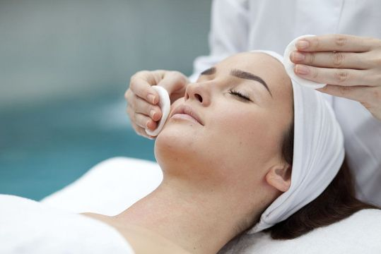 Woman lying down with eyes closed receiving chemical peel