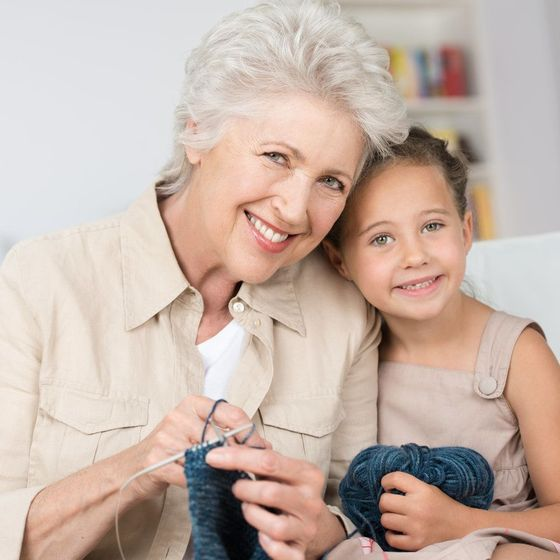 Smiling woman posing with granddaughter and knitting materials