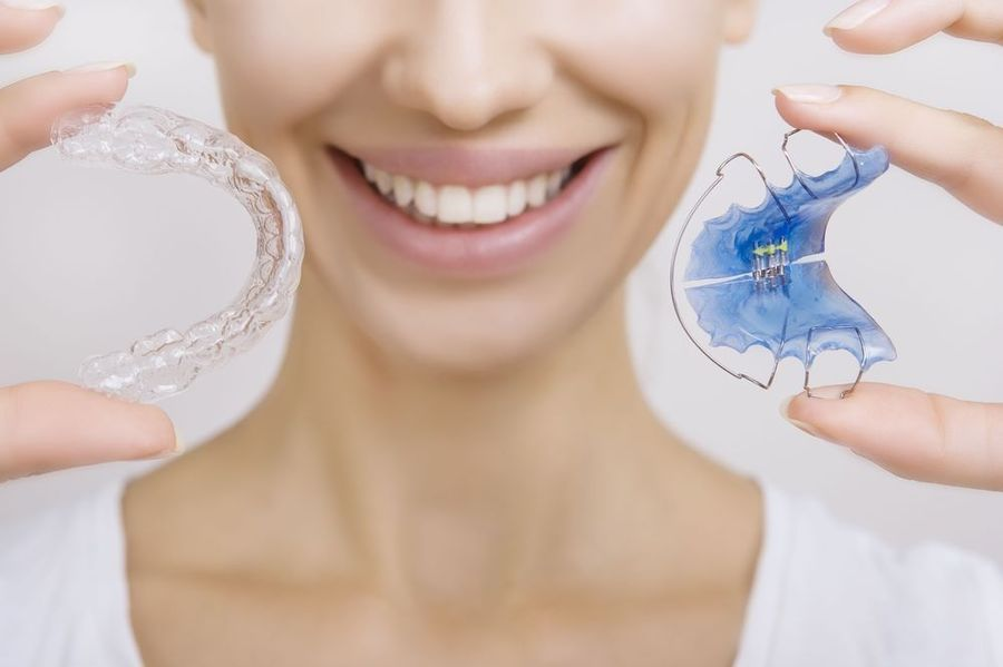 photo of woman holding a clear aligner tray and retainer