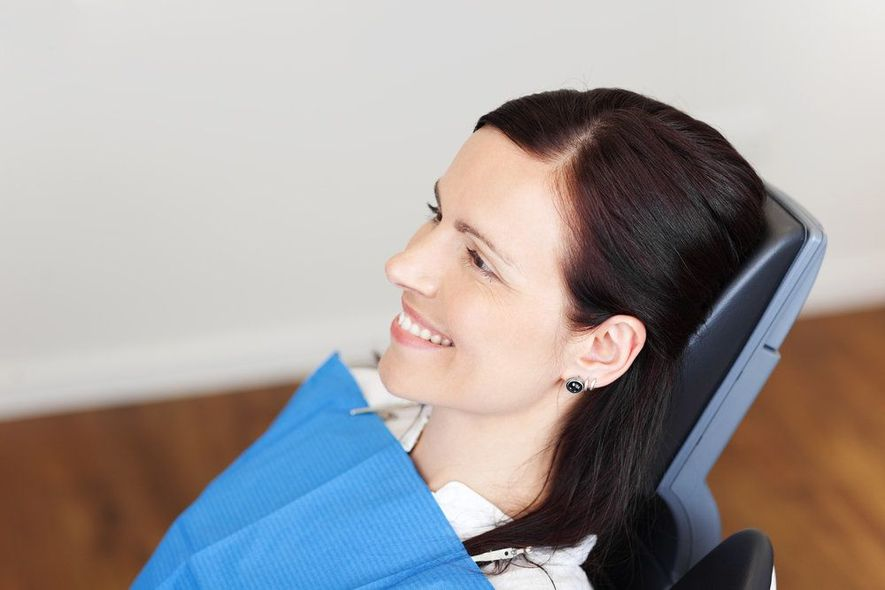 Brunette woman smiling while sitting in a dental chair