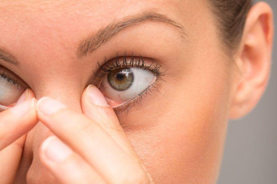 Woman rubbing red eyes