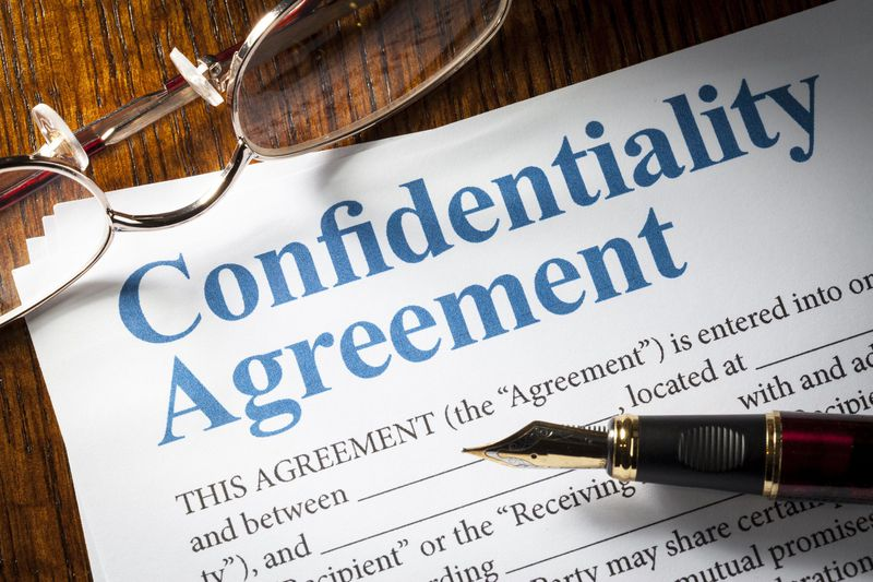 Photo of a pen and glasses by a confidentiality agreement