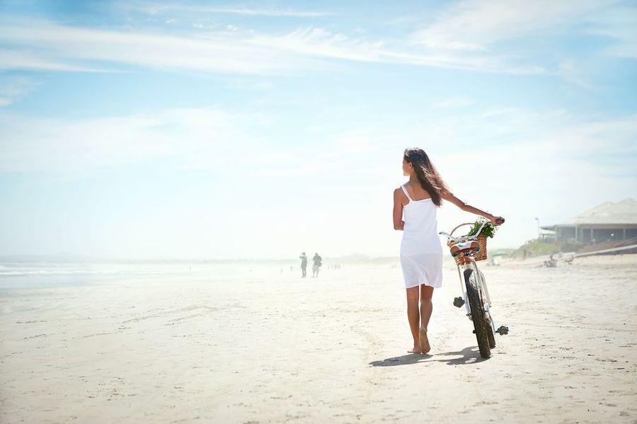 Slim woman in white dress walking bike on beach