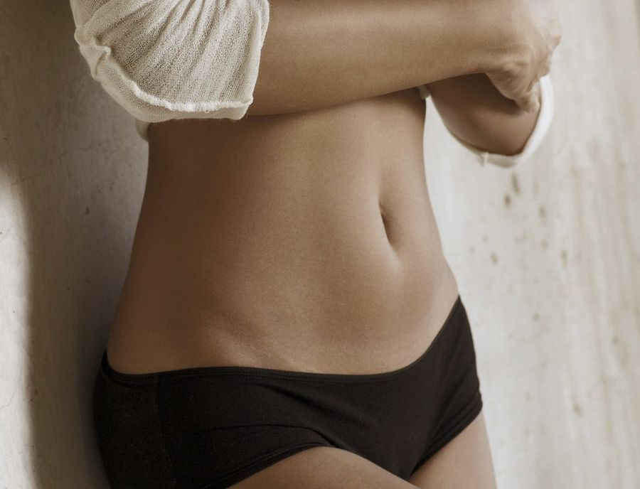 Woman's slim midsection with shirt pulled up