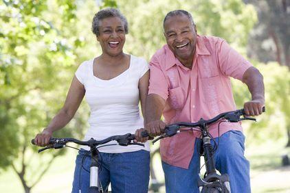 Older couple smiling while riding bikes