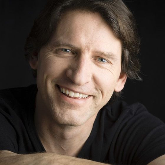 Smiling dark-haired man in a black t-shirt