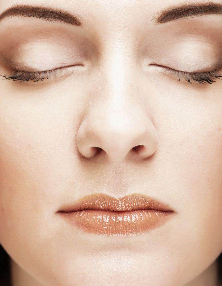 Un primer plano facial de una mujer con piel lisa, cejas oscuras, ojos cerrados y lápiz labial oscuro de color nude.