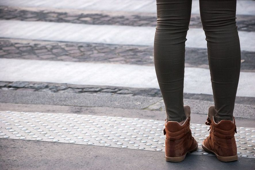 Woman's legs at edge of crosswalk