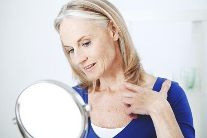 A woman looking at her neck in the mirror