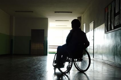Photo of a person in a wheelchair lit from behind
