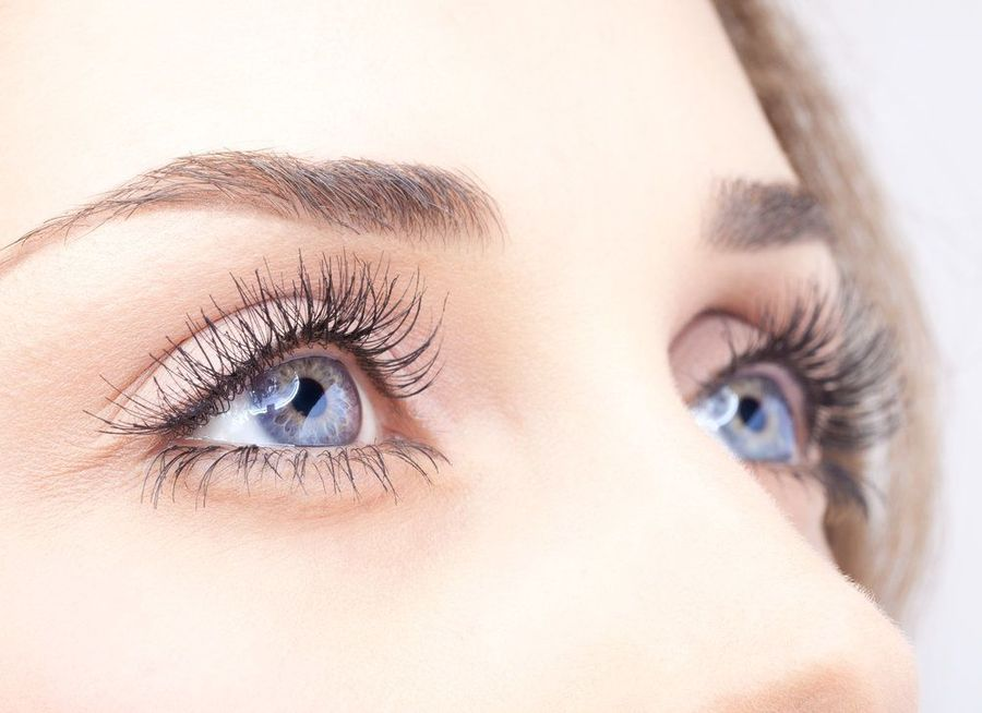 A woman with dazzling blue eyes and long eyelashes looks upward and to the side.