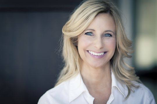 Smiling blonde woman with a white shirt