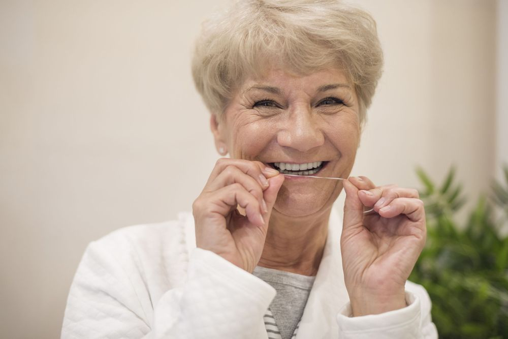 Older woman smiling as she hold up floss.