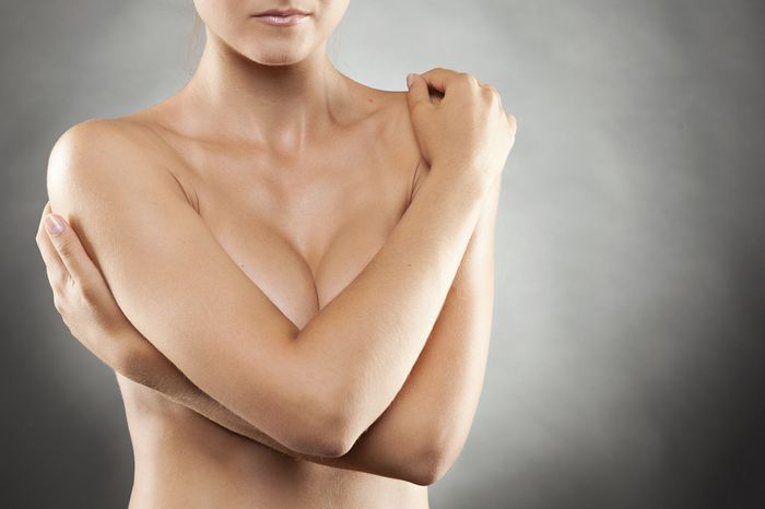Naked woman protectively folding arms over breasts