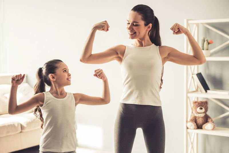 Mother and daughter flexing arms