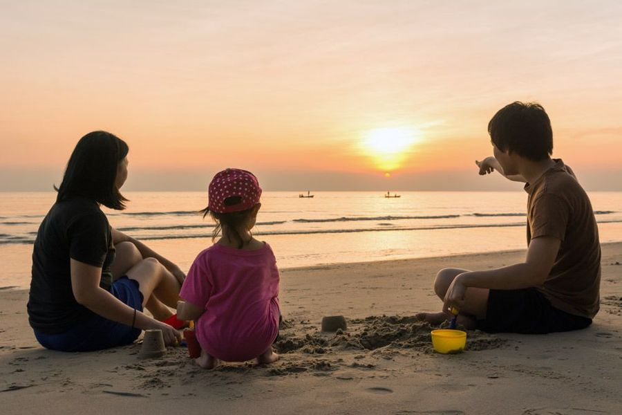 Parents and young child watching sunset on beach