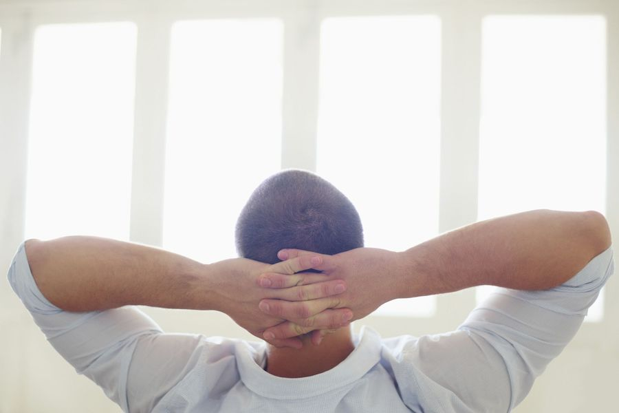 Man relaxing with his hands behind his head