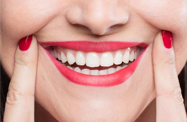 Smiling woman with red nails and lips