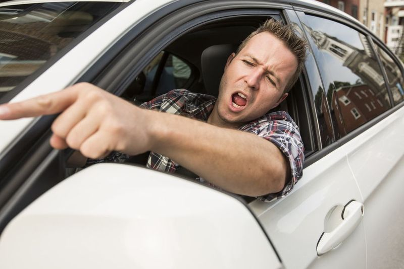 A driver pointing angrily out of his car window