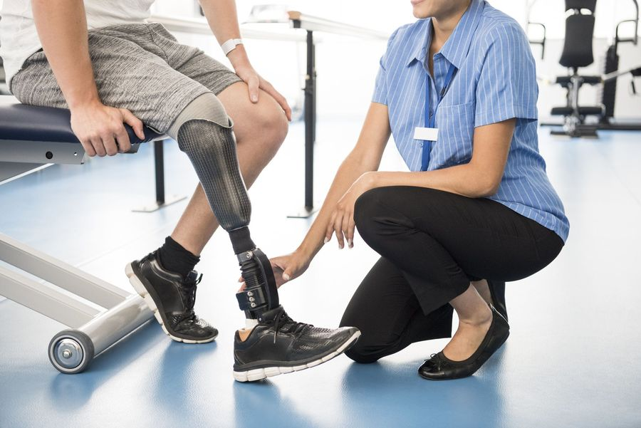 Medical professional kneeling to look at a man's prosthetic leg