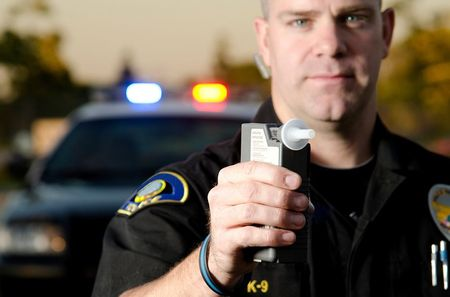 Police officer holding a breathalyzer device.