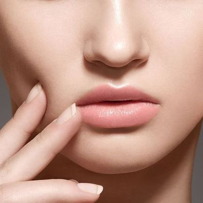 Facial Plastic Surgeon: close-up of a woman's lips as she rests a hand against her face