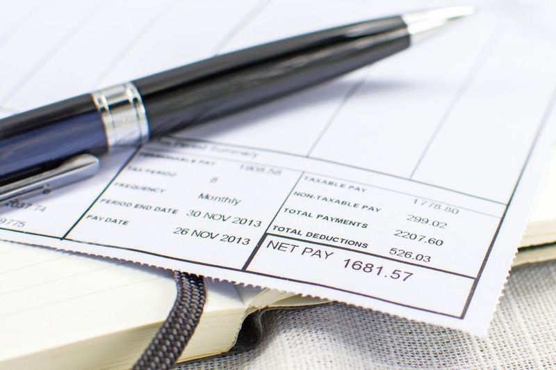 A pen sits on top of a paycheck stub