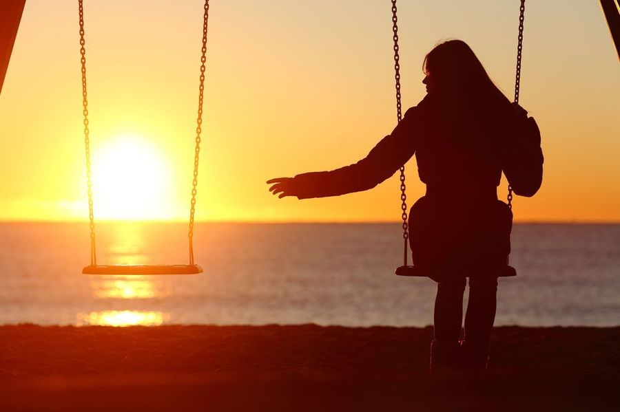 Woman on swing alone reaching out to empty seat in front of sunset over ocean