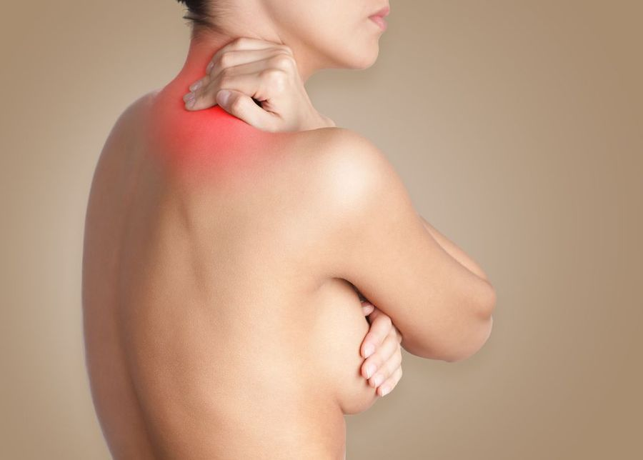 Woman holding neck in pain and covering breast