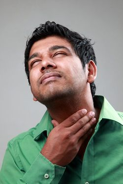 young man grasping sore throat
