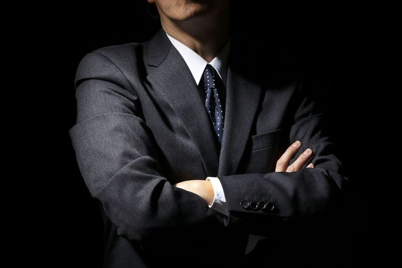 Man in business suit with crossed arms standing in shadow