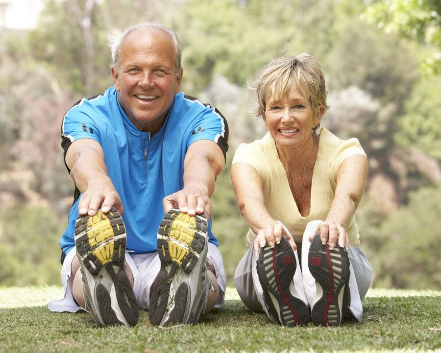 Man and woman stretching in the grass