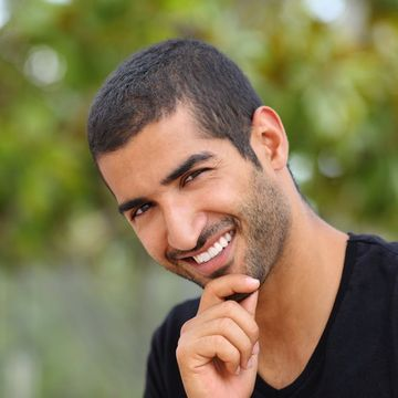 A young man in a black shirt smiling outdoors