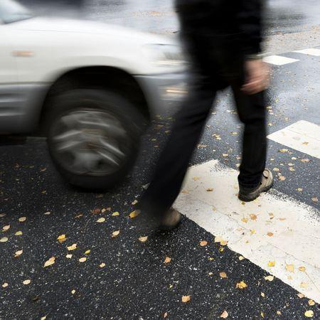 A blurry photo of a car about to strike a pedestrian in a crosswalk