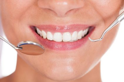 Close-up of a woman's smile with a dental mirror and tool nearby