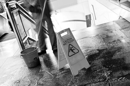 Wet floor sign with blurred image of man mopping