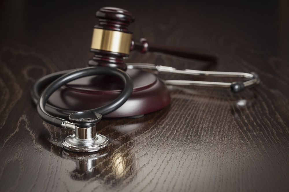View of medical heart monitor and judge's gavel on desktop