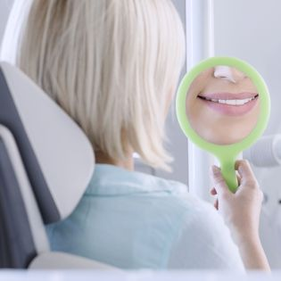 A woman examines her teeth in a handheld mirror
