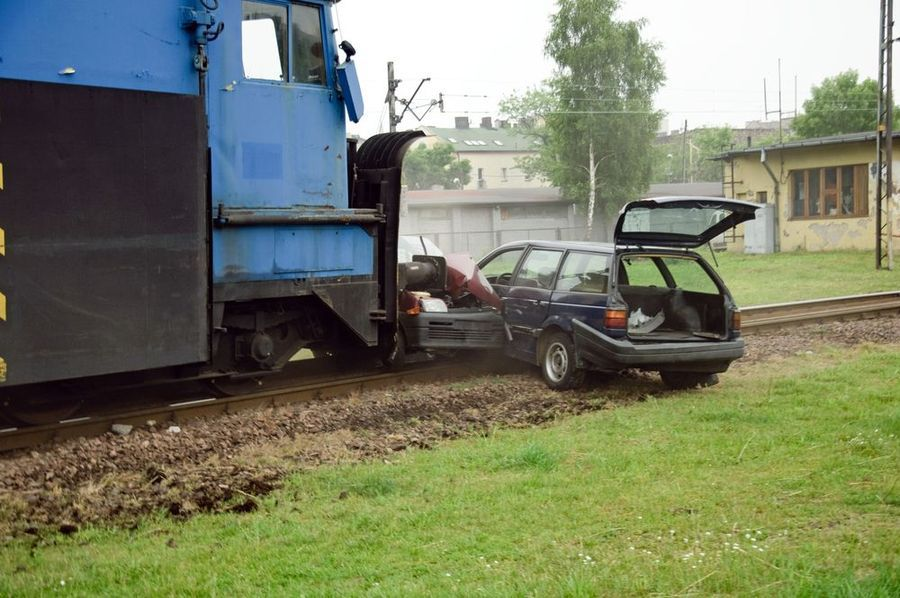 Two wrecked cars on the tracks in front of a train