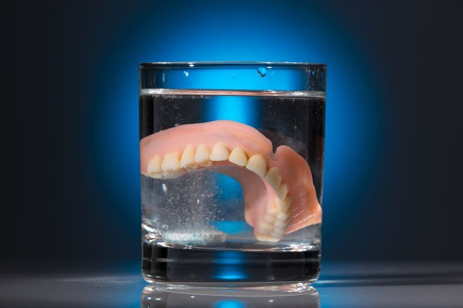 Denture in a glass of cleaning fluid