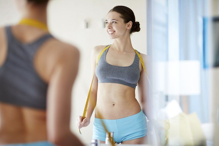 Woman in sports bra with measuring tape