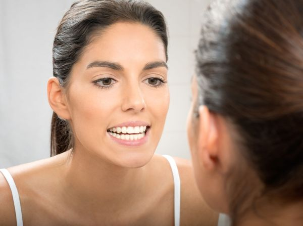 A woman looking at her smile in the mirror