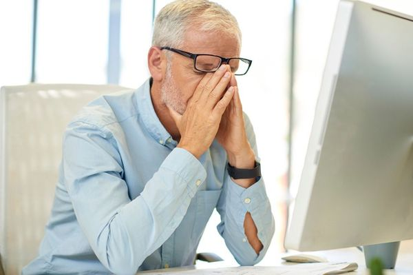 Image of older man holding his face in his hands