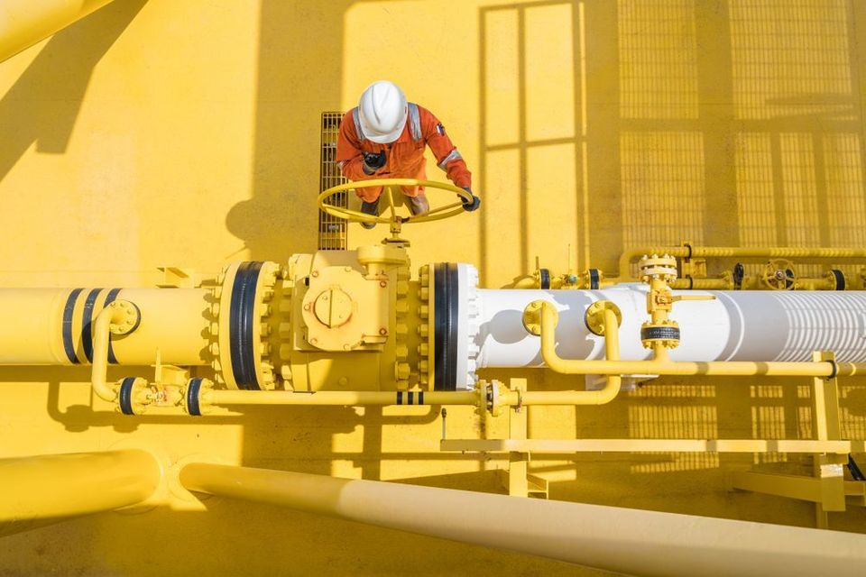 Worker tightening the valve on a large yellow pipe