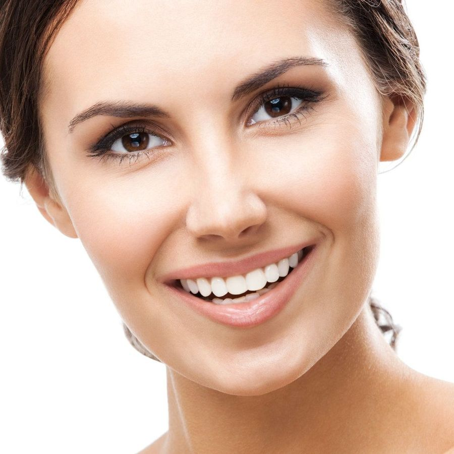 A beautiful woman smiles with beautiful, brown eyes and hair, pink lips, and uniformly straight, white teeth.