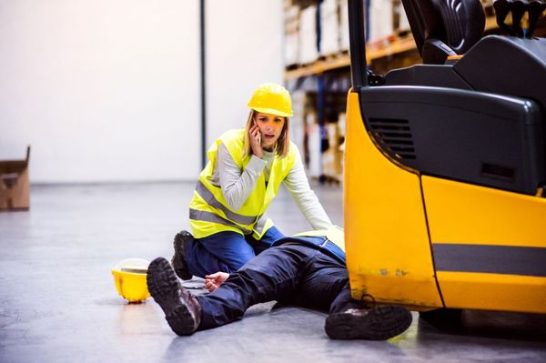 A woman on a phone kneels next to a man whose foot is pinned under a forklift