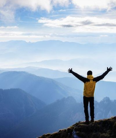 A man at the top of a mountain spreads his arms