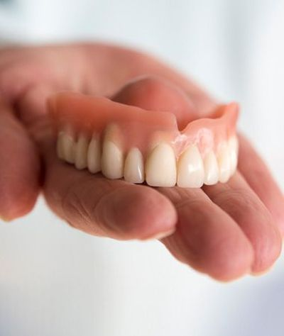 A hand holding dentures