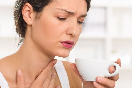 Woman holding a teacup with one hand to her throat