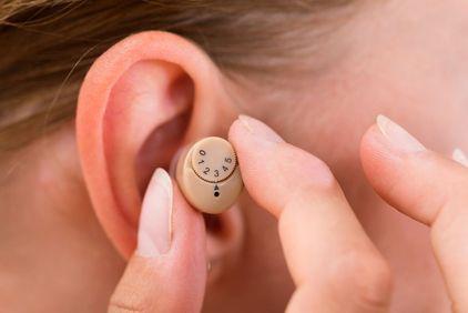 Two fingers holding a hearing aid near an ear